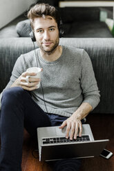 Portrait of confident young man with laptop and headphones at home - GIOF02894