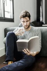 Young man reading book at home - GIOF02897