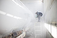 Industrial worker spray painting and wearing protective clothing - ZEF14057