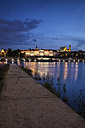 Poland, Warsaw, Old Town skyline with Royal Castle at night, view from pier on Vistula River - ABOF00234