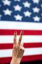 Woman's hand showing victory sign in front of American Flag - MAUF01146