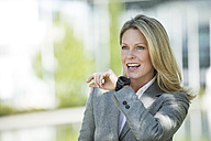Smiling businesswoman with smartwatch outdoors - MAEF12244