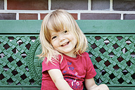 Portrait of smiling little girl on garden bench - EVGF03235