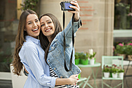 Laughing girlfriends taking a selfie in the street - CHAF01891