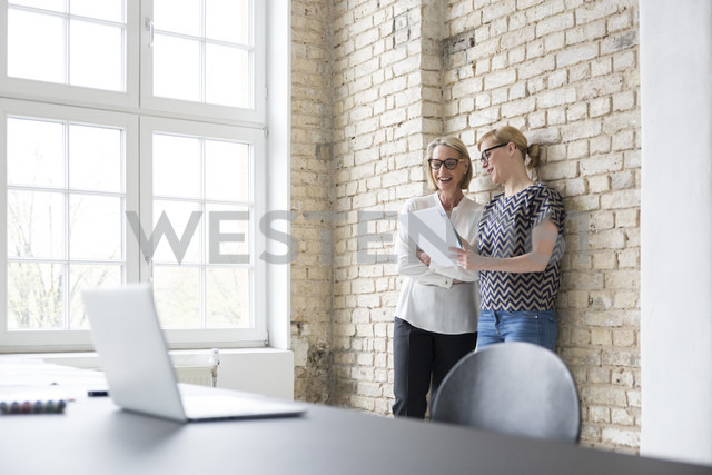 Mature businesswoman working with younger colleague in office - RBF05754