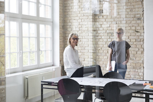 Mature businesswoman working with younger colleague in office - RBF05757
