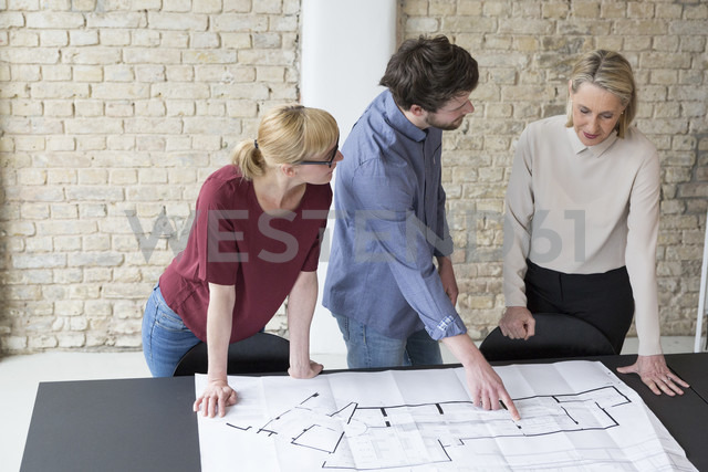 Mature businesswoman working with younger colleagues in office - RBF05763