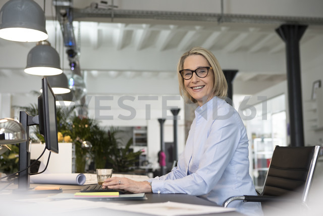 Mature businesswoman working in office, smiling - RBF05772