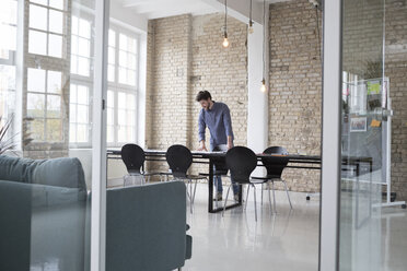 Young entrepreneur standing in his office, looking at plans - RBF05805