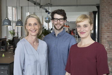 Three smiling businesspeople in office - RBF05817
