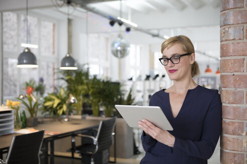 Portrait of a businesswoman in office, using digital tablet - RBF05823