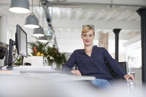 Businesswoman sitting at desk - RBF05832
