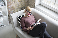 Woman sitting on couch, reading book - RBF05838