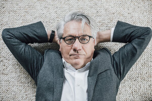 Portrait of senior businessman lying on the floor - GUSF00011