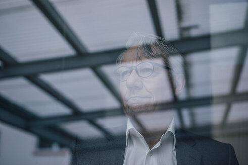 Senior businessman behind windowpane - GUSF00029