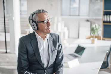 Senior businessman listening to music with headphones in office - GUSF00038