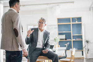 Senior businessman talking to young businessman in office - GUSF00041