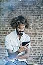 Young man checking his tablet - KNSF01711
