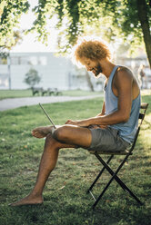 Man with beard and curly hair using laptop in park - KNSF01717