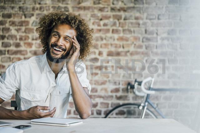 Happy young man at desk - KNSF01723