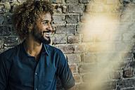 Smiling man with beard and curly hair at brick wall - KNSF01738