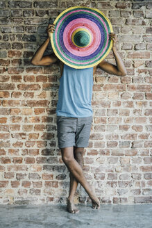 Man standing at brick wall covering his face with a sombrero - KNSF01744