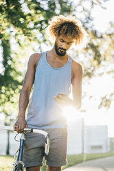 Young man with bicycle checking cell phone - KNSF01747