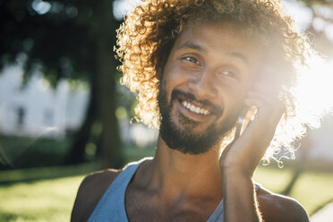 Portrait of smiling young man on cell phone - KNSF01750