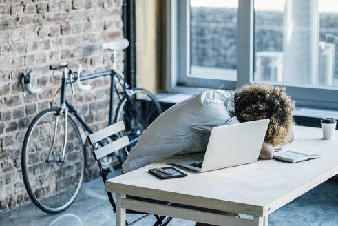 Young man lying on desk - KNSF01753