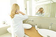 Woman looking at her mirror image in the bathroom - MAEF12246