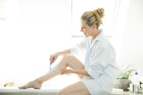 Woman sitting on edge of bathtub shaving her leg - MAEF12252