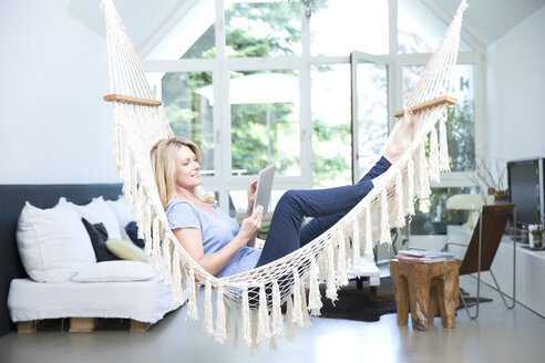 Blond woman with tablet relaxing in hammock in the living room - MAEF12258