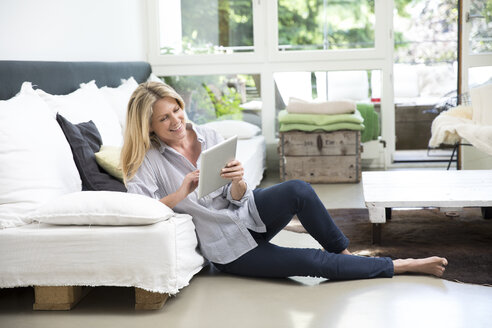 Relaxed woman sitting on floor of the living room using tablet - MAEF12264