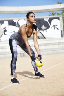 Fit woman exercising with kettlebell outdoors - SUF00182