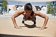 Fit woman doing pushups outdoors - SUF00188