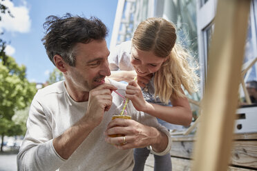 Father and daughter sharing drink at an outdoor cafe - SUF00209