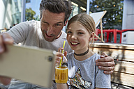 Playful father and daughter taking a selfie at an outdoor cafe - SUF00212