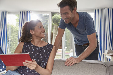 Happy couple using tablet at home - SUF00230