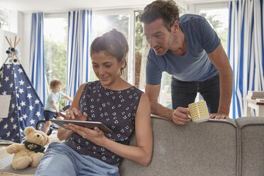 Couple using tablet at home with boy in background - SUF00233