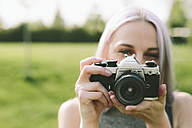 Young woman taking pictures with camera in nature - GIOF02902