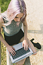Young woman with pink grey hair using laptop - GIOF02905
