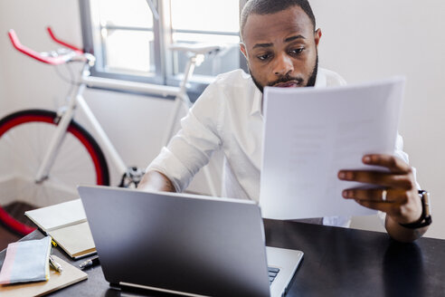 Man looking at papers at desk in home office - GIOF02917