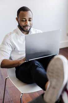 Man using laptop in home office with feet on desk - GIOF02923