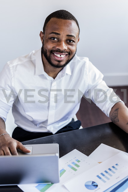 Portait of smiling man analysing data and using laptop at desk in home office - GIOF02932 - Giorgio Fochesato/Westend61