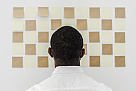 Man looking at adhesive notes on wall in office - GIOF02941
