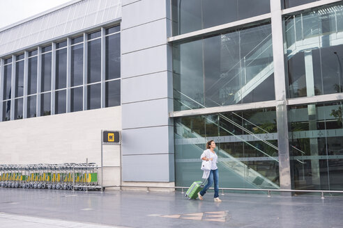 Woman walking with rolling suitcase outside airport building - SIP01641