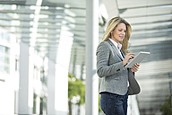 Businesswoman using tablet outdoors - MAEF12270