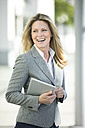 Happy businesswoman holding tablet outdoors - MAEF12273