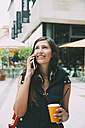 Portrait of smiling young woman on cell phone with takeaway drink in the city - CHAF01909
