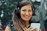 Portrait of smiling young woman with headphones and cell phone in the city - CHAF01912